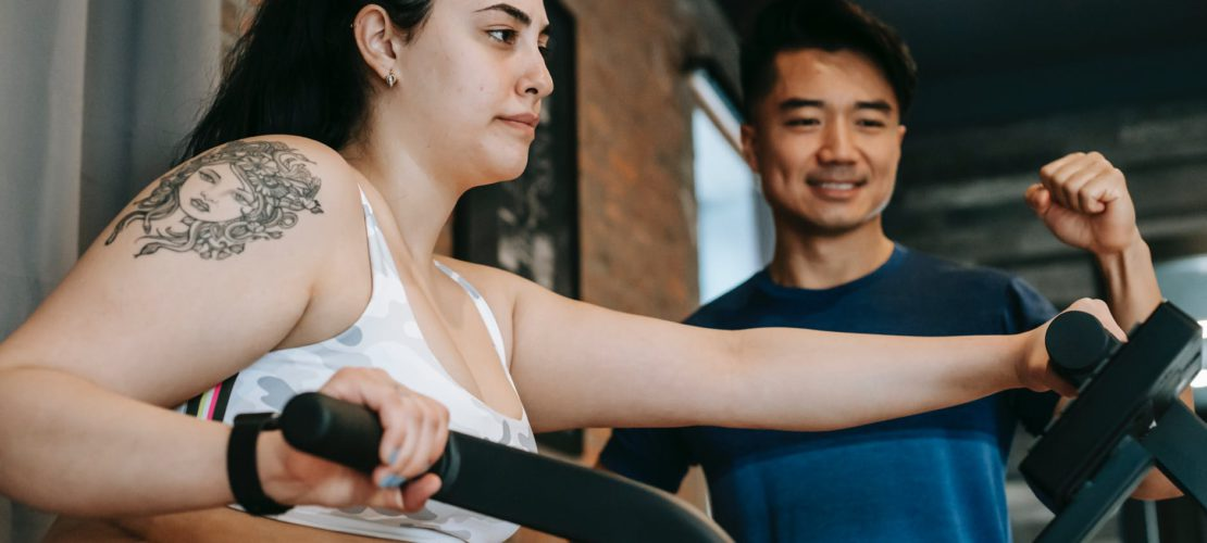 serious young overweight woman doing cardio exercise on elliptical machine with ethnic instructor