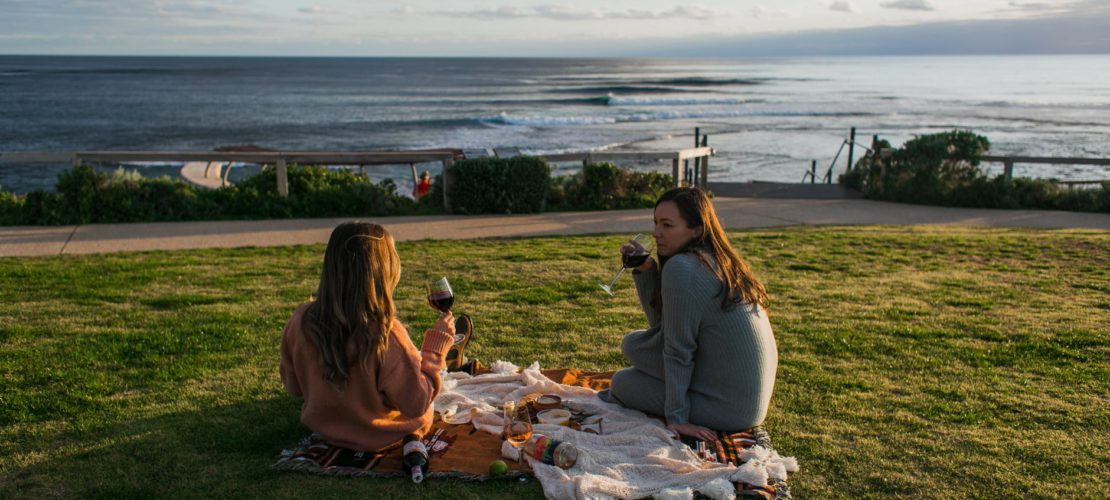 women drinking wine during picnic on seashore